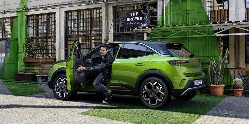 zöld elektromos Opel Mokkából kiszálló férfi